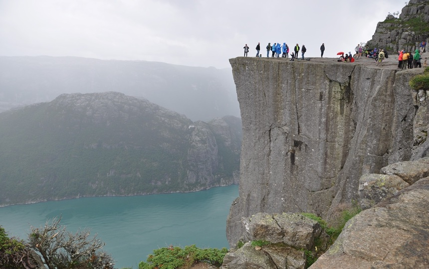 Hikers looking out from Preikestolen cliff, one of the most famous tourist sights in all of Norway.