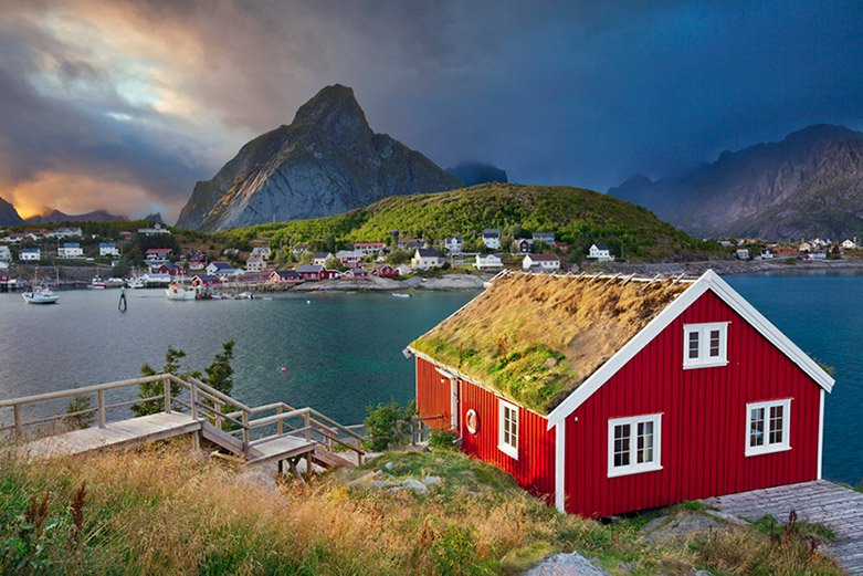 Red cabin in Norway with the Lofoten mountains in the background