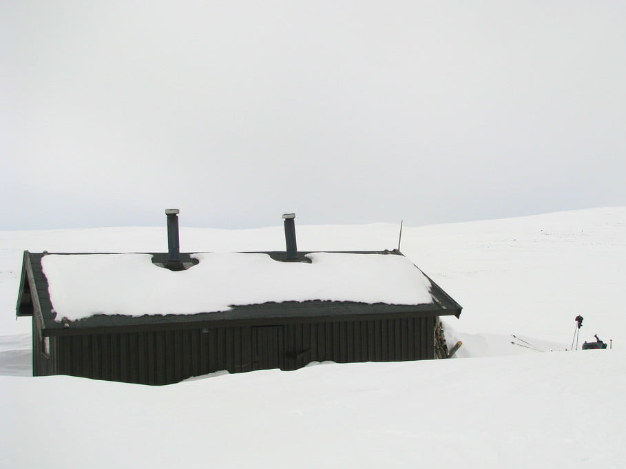 Remote cabin part-buried in snow on the Finnmark plateau in northern Norway.