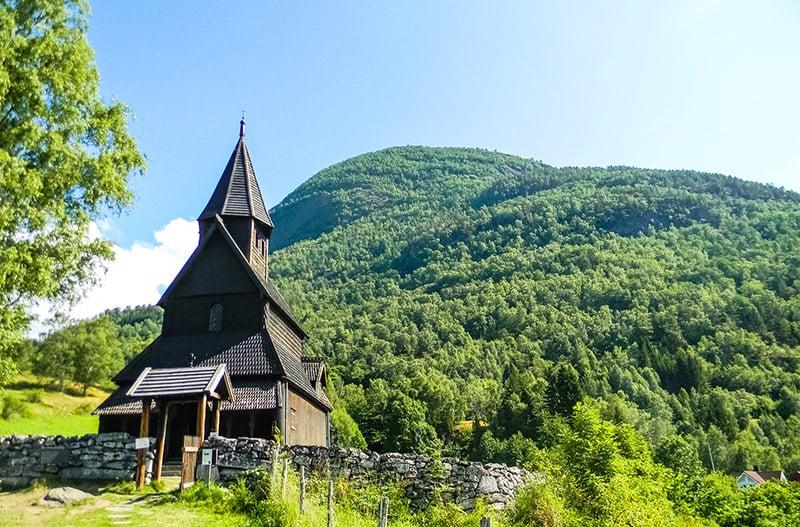 Urnes stave church in a green field in Norway