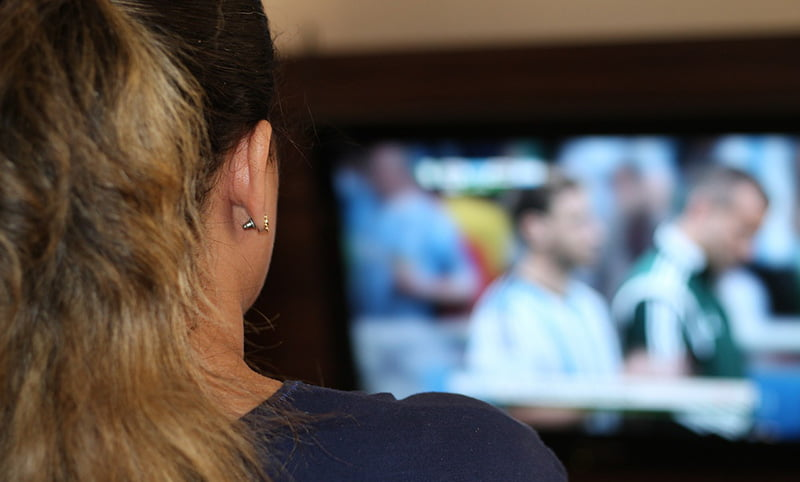 A woman watching football on TV in Norway