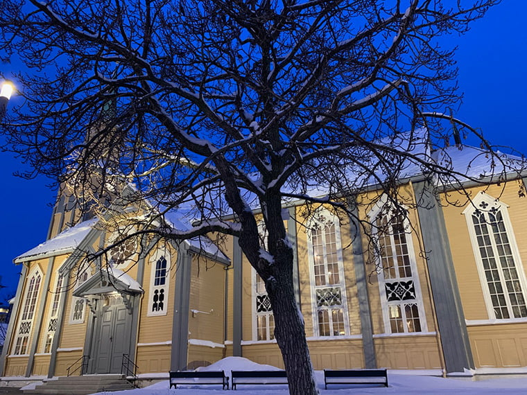 The beautiful wooden cathedral of Tromsø bathed in winter blue light