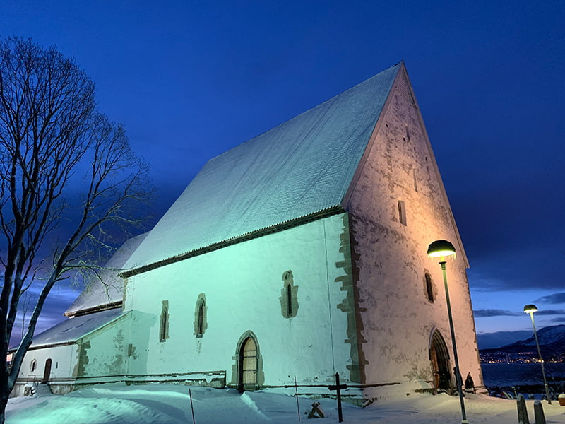 Trondenes Church bathed in stunning polar light. The stone church is in Harstad, Norway