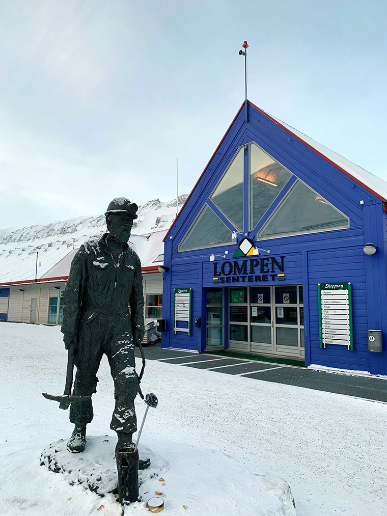 Coal miner sculpture and Lompen shopping centre in Longyearbyen, Svalbard
