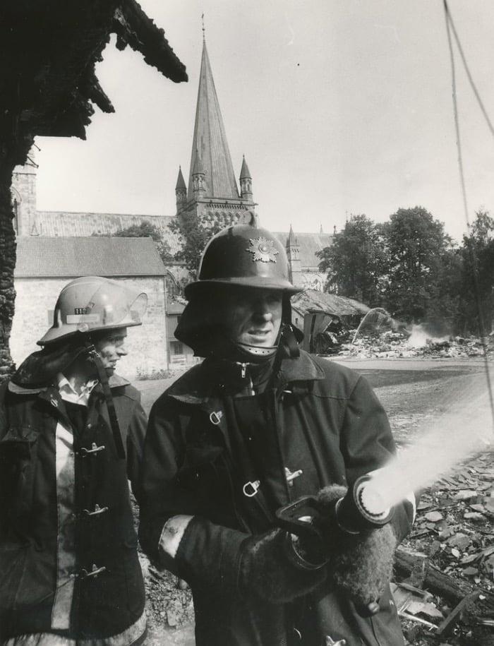 A Norwegian firefighter tackles a blaze in Trondheim, Norway