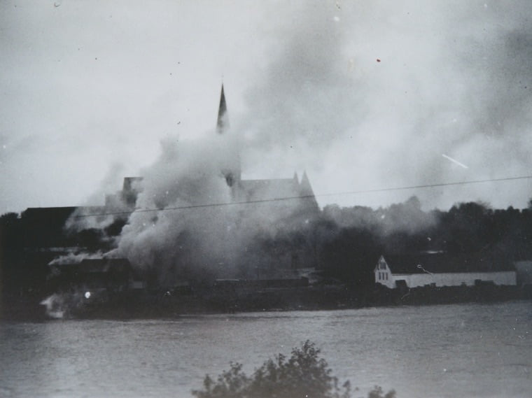 Nidaros Cathedral stands in the background as a wooden building burns in Trondheim, Norway