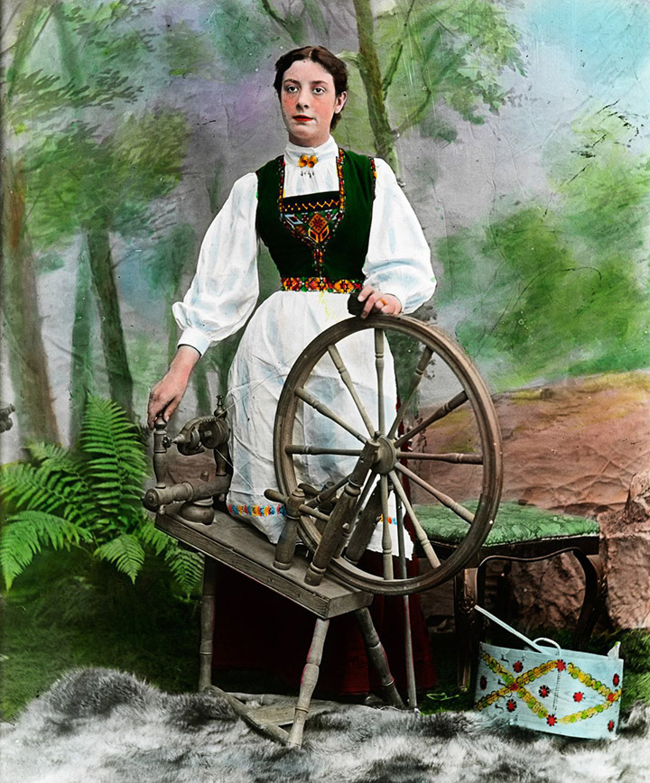 Norwegian woman in the national costume with a spinning wheel