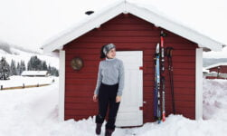 Mon Amie standing in front of a Norwegian cabin in the snow