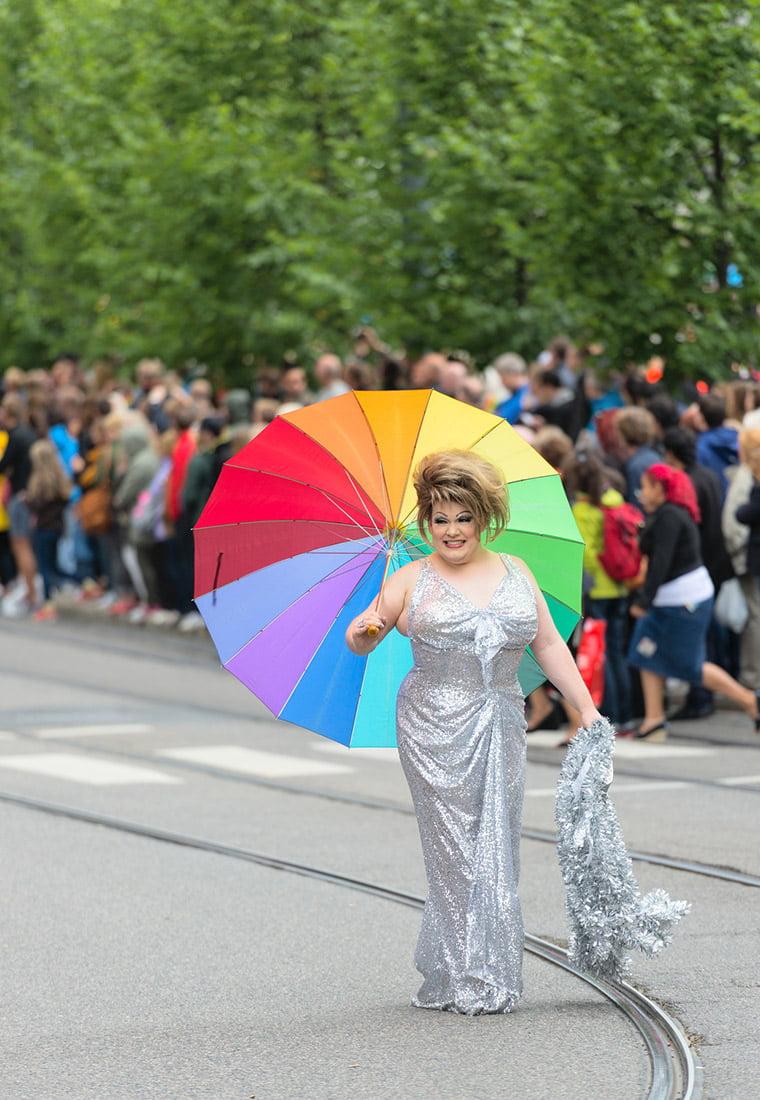 A happy participant in the Oslo Pride parade holding a rainbow umbrella