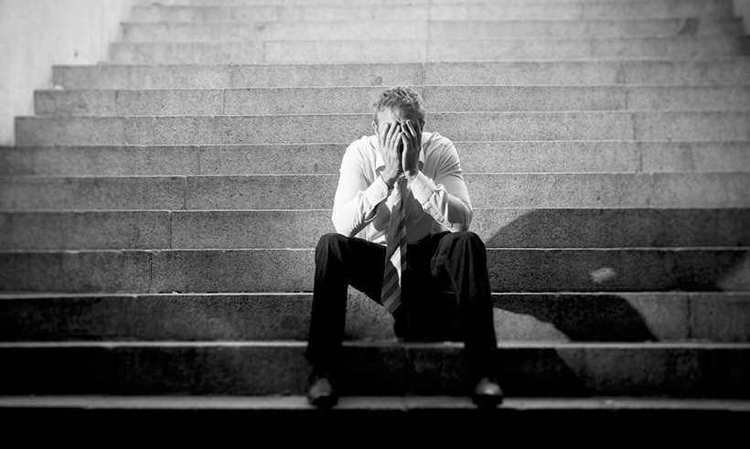 An unemployed person slumped on steps in Oslo, Norway