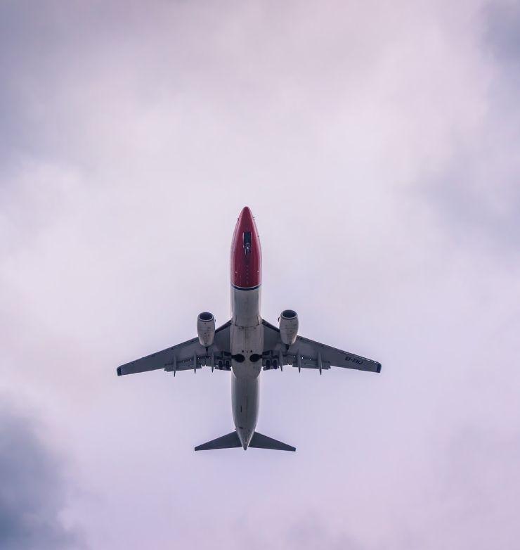 Norwegian Air airplane flying in the sky from below