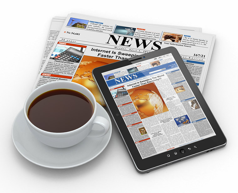 A physical newspaper, online news website, cup of coffee