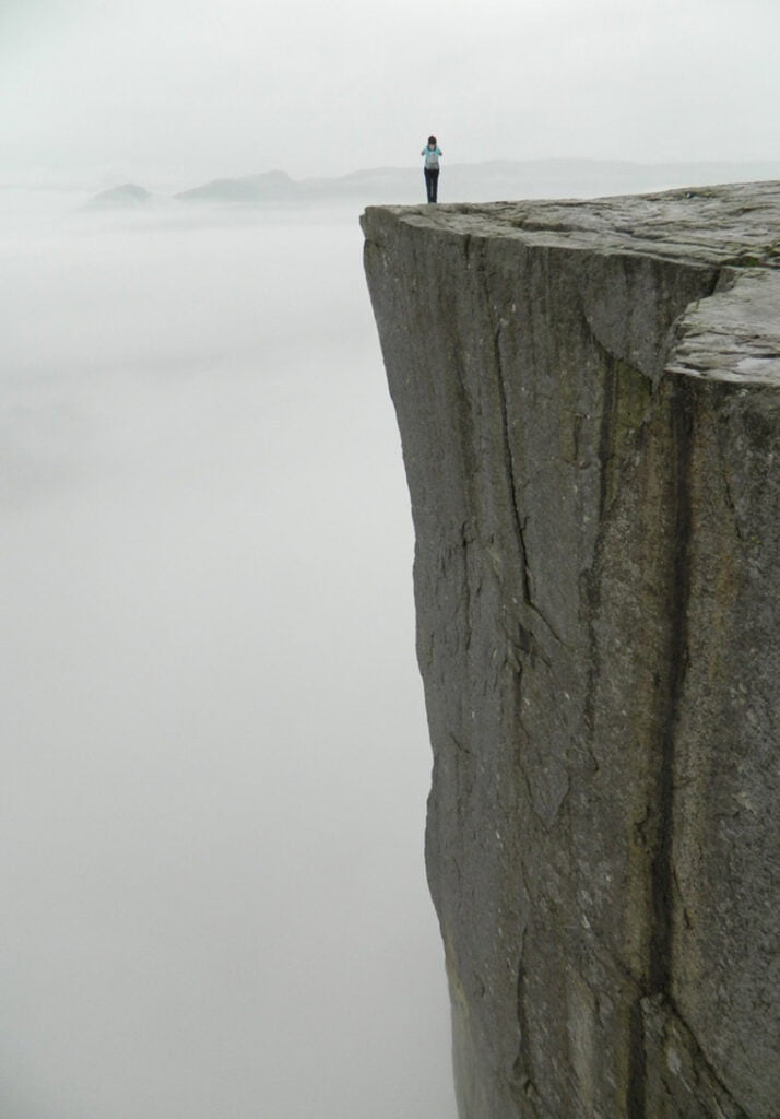 Norwegian standing on the Preikestolen cliff on a foggy day