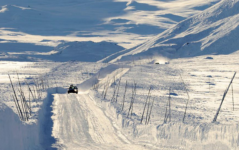 A car driving on the snow-covered Valdresflye mountain road in central Norway