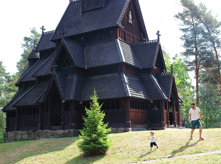 Father and son playing in front of the Gol Stave Church at the Norwegian Museum of Cultural History in Oslo