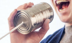 Man speaking Norwegian into a tin can telephone