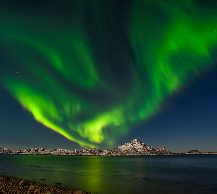 An aurora borealis display in bright green above Senja, northern Norway