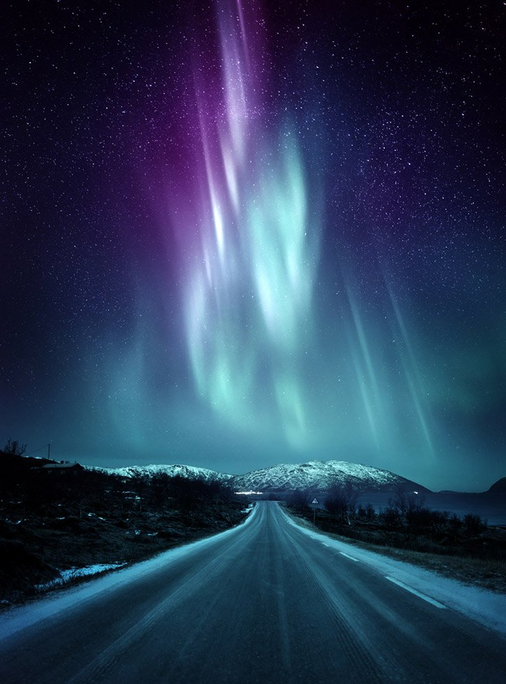 The northern lights above an Arctic road in northern Norway