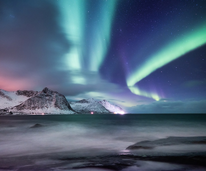 A northern lights display above the mountains of Senja island in Norway