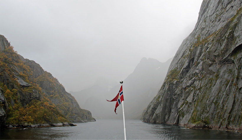 A boat with a Norwegian flag sailing into Norway's Trollfjord