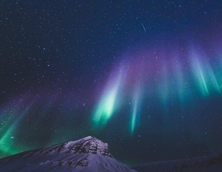 An aurora borealis display of green and purple lights above Longyearbyen, Svalbard