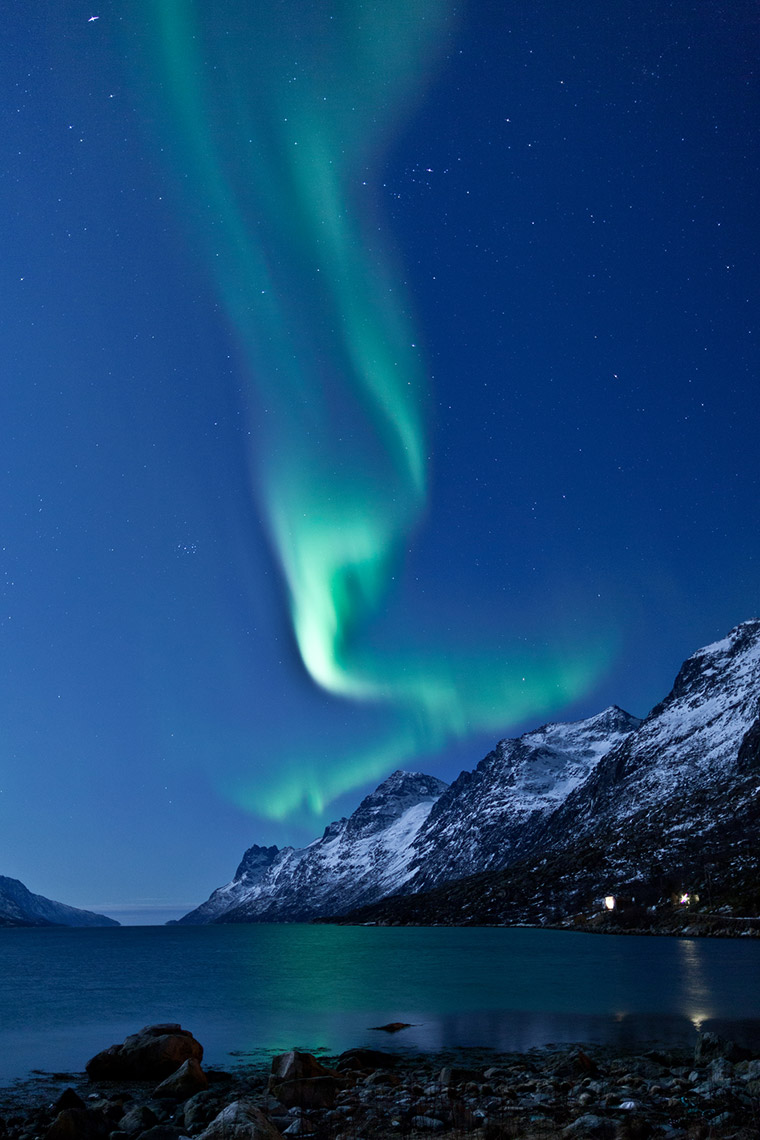 Green northern lights above a mountain in a Norwegian winter