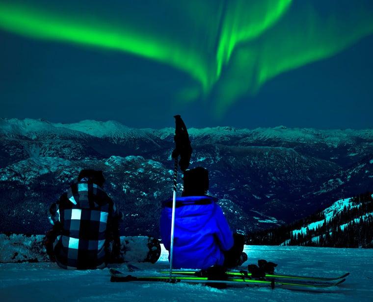 Skiers watching the aurora borealis in Northern Norway