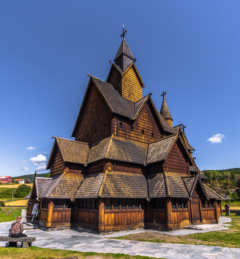 A man sitting outside Norway's Heddal wooden church