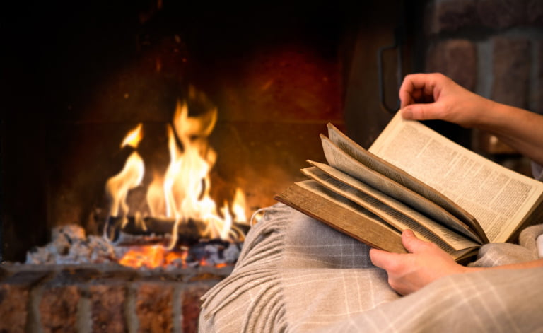 Reading a Norway book by the fireplace