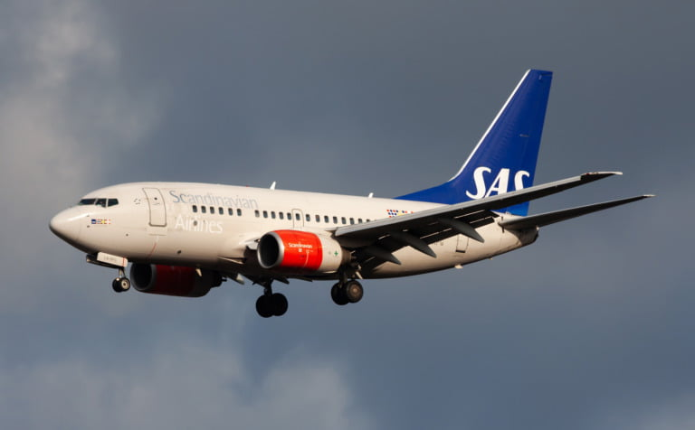 SAS (Scandinavian Airlines) airplane against a stormy sky.