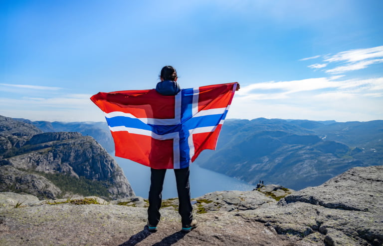 Hiker in the Norwegian mountains holding the flag of Norway