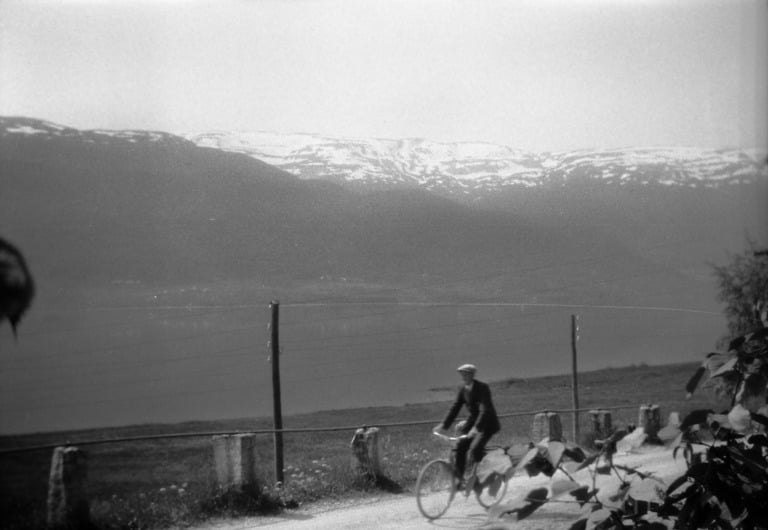 A cyclist in Voss, with the mountains in the background.