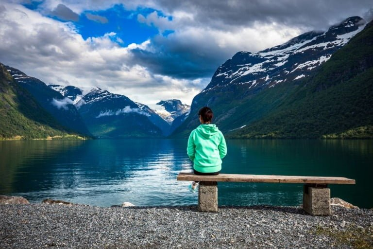 A hiker contemplating the peaceful lake Lovatnet in fjord Norway