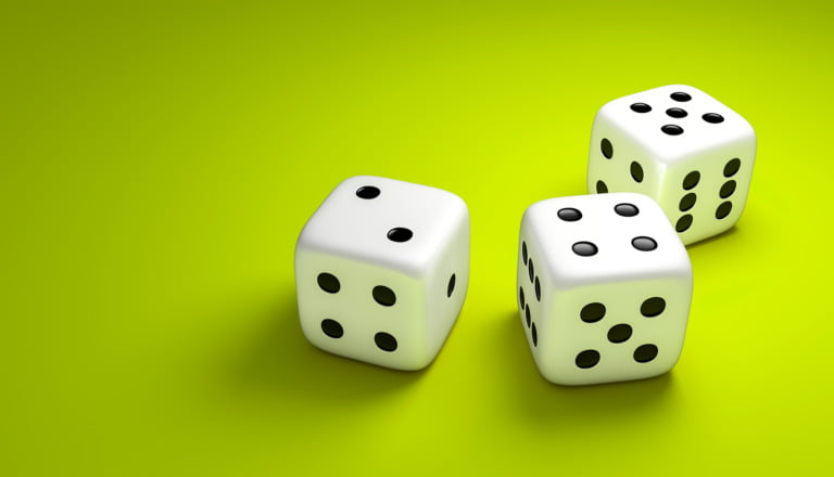 Three dice on a green background