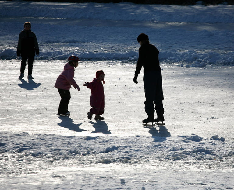 Scandinavian family ice skating in the winter.