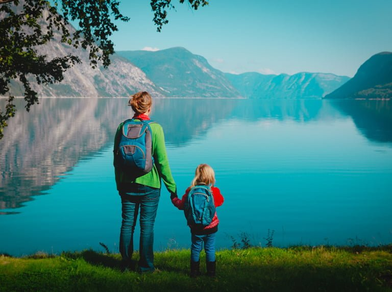 Mother and girl standing by a Norwegian fjord