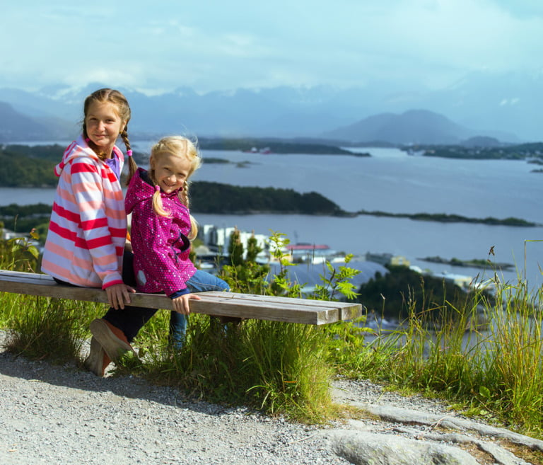 Two Norwegian girls sitting by a fjord in Norway