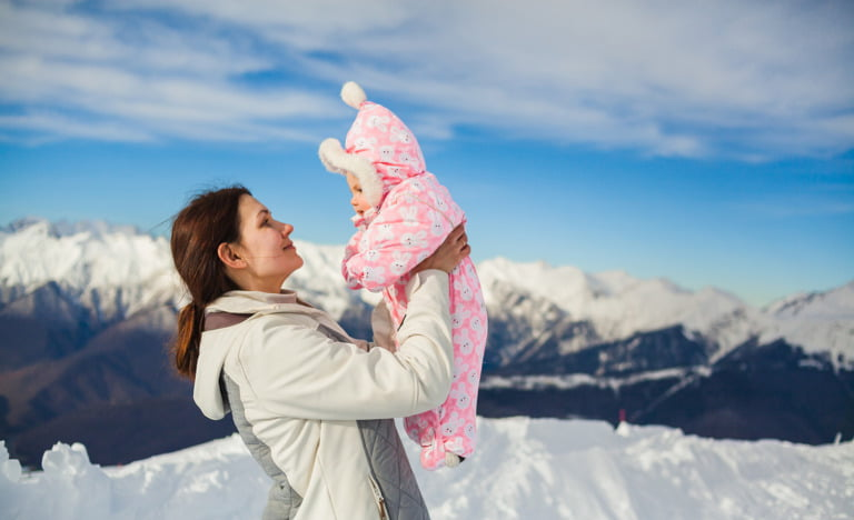 Mother and new baby in Norway with snowy landscape