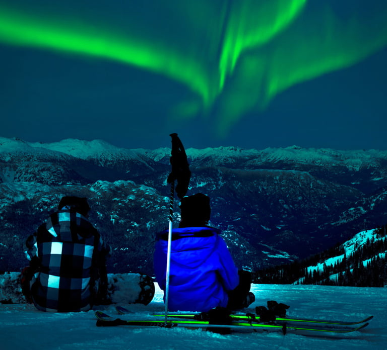 Skiers watching the northern lights in Norway