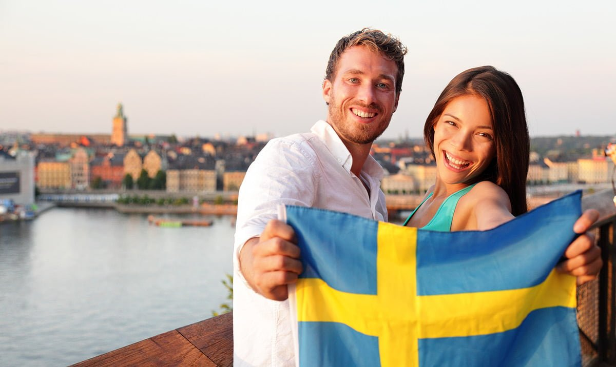 Two Swedish people holding the flag of Sweden in Stockholm