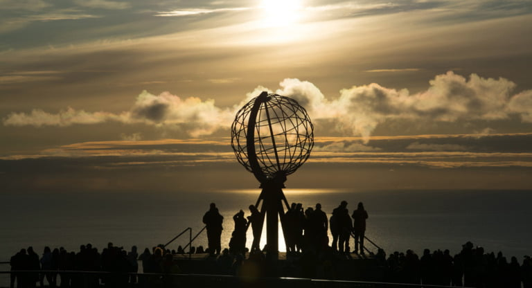 Crowds gather around the globe sculpture at Nordkapp in Norway.