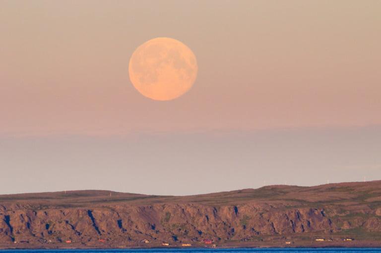 A full moon in the midnight sun over Varangerhalvøya National Park