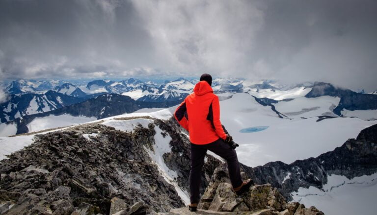 Hiker admiring the view from Galdhøpiggen mountain in Norway.