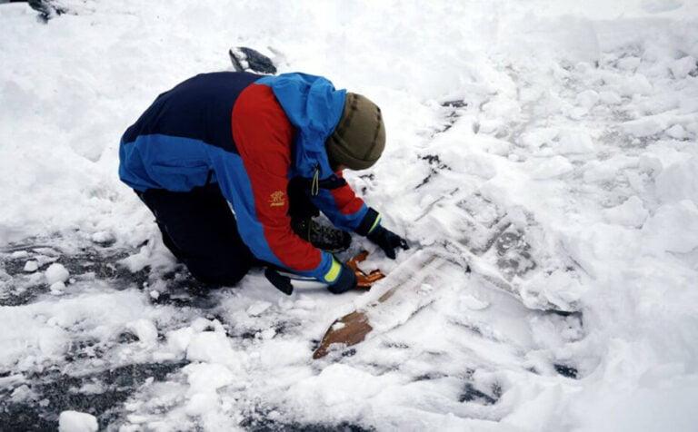 Julian Post-Melbye shovels away snow around the ski.